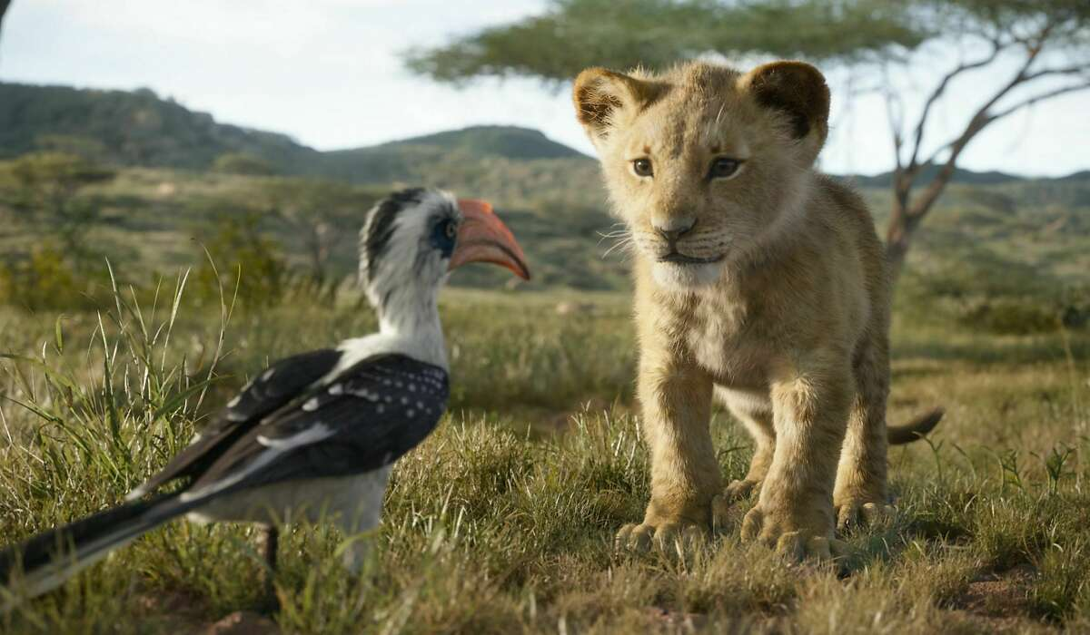 """This image released by Disney shows characters, from left, Zazu, voiced by John Oliver, and young Simba, voiced by JD McCrary, in a scene from """"The Lion King."""" (Disney via AP)"""