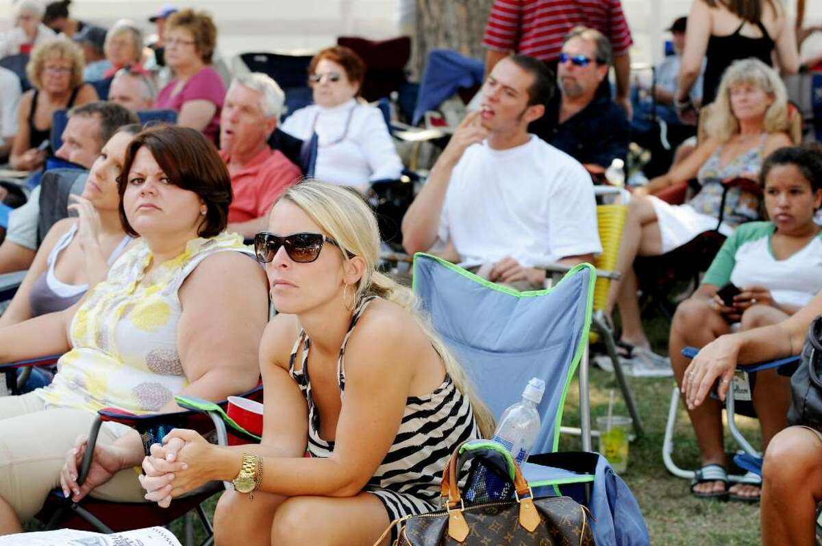 Track goers sit adjacent to the paddock at Saratoga Race Course the as they await results of the fourth race on Sunday. (Luanne M. Ferris / Times Union)