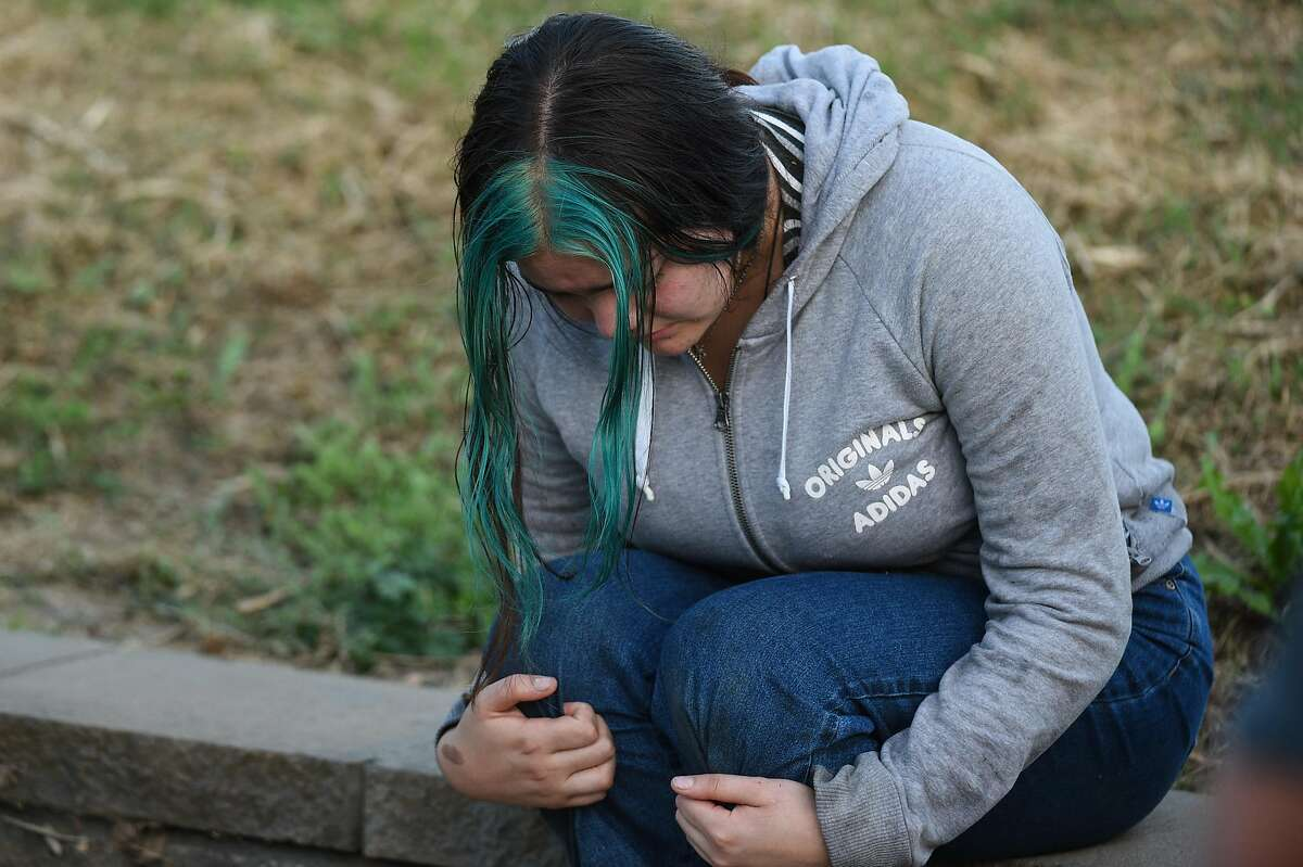 An unidentified woman reacts at the scene of a shooting during the Gilroy Garlic Festival along Miller Avenue near Gilroy High School on July 28, 2019 in Gilroy, CA.