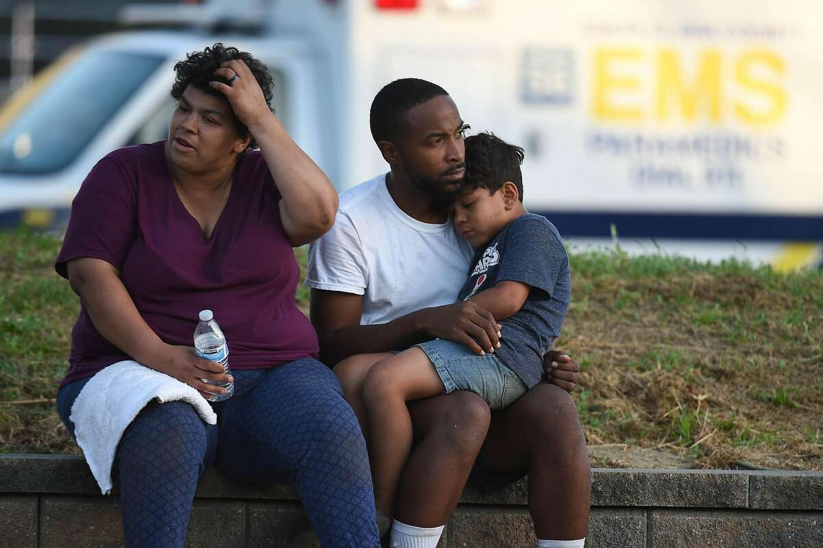 Unidentified attendees react outside the scene of a shooting during the Gilroy Garlic Festival along Miller Avenue near Gilroy High School on July 28, 2019 in Gilroy, CA.