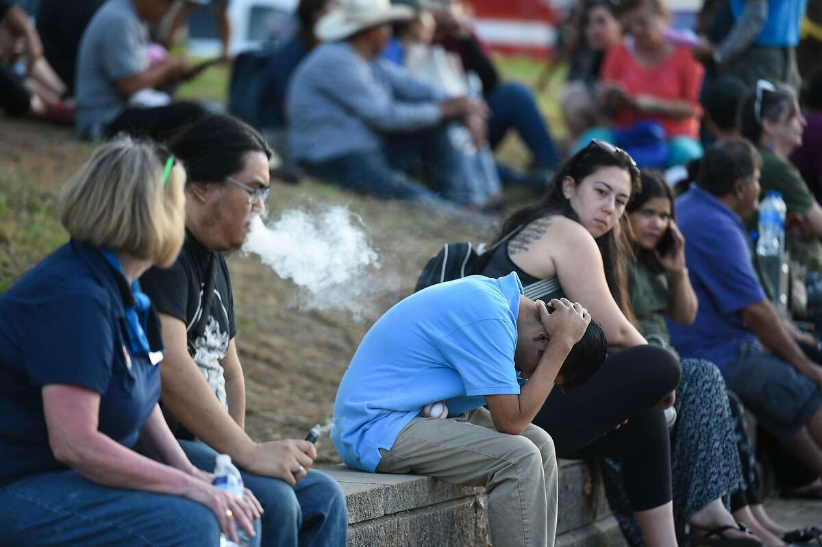 Attendees react at the scene of a shooting during the Gilroy Garlic Festival along Miller Avenue near Gilroy High School on July 28, 2019 in Gilroy, CA.