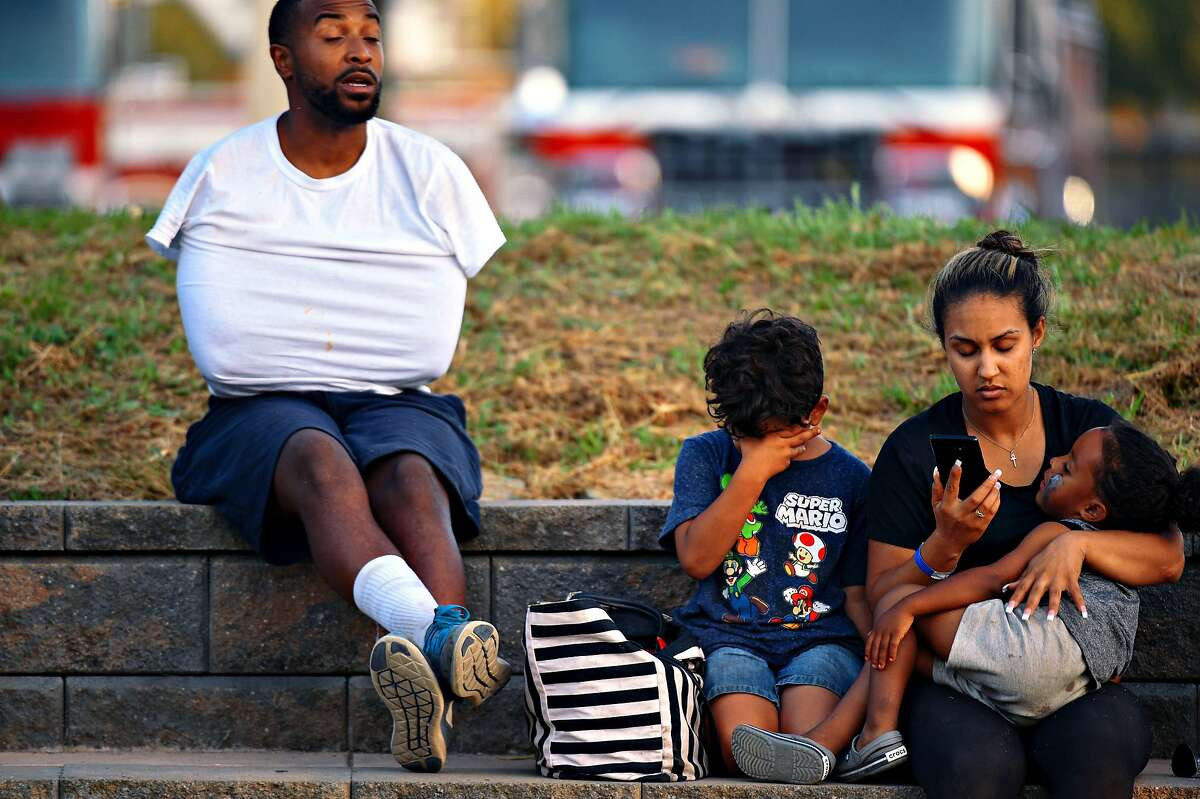 A family reacts at the scene of a shooting during the Gilroy Garlic Festival along Miller Avenue near Gilroy High School on July 28, 2019 in Gilroy, CA.