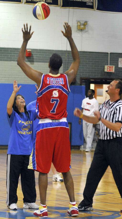 Photography by PETER HVIZDAK ph934 #2622 West Haven, Connecticut- 10/15/08: Gina Prisco, principal of Pagels School in West Haven, left, and the Harlem Superstars basketball player Rick The 7 footer Lopez squares off for a jump ball at the start of the comedy basketball fundraising game at West Haven High School Wednesday night for the Pagels School Enrichment Program. Photo: /