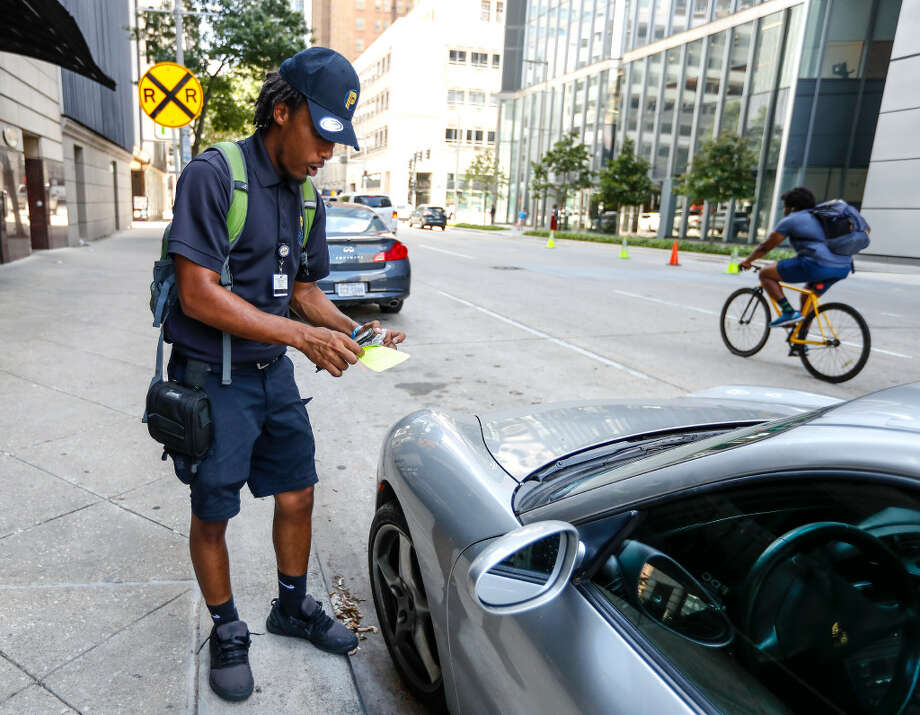 Morgan Metoyer, a city of Houston parking ticket officer, prepares to place a ticket on the windshield of a car parked in downtown Houston on lower Westheimer. >>>See some parking tickets by block. Photo: Karen Warren/Houston Chronicle
