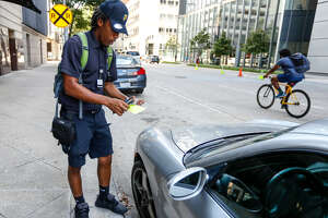 Morgan Metoyer, a city of Houston parking ticket officer, prepares to place a ticket on the windshield of a car parked in downtown Houston on lower Westheimer.