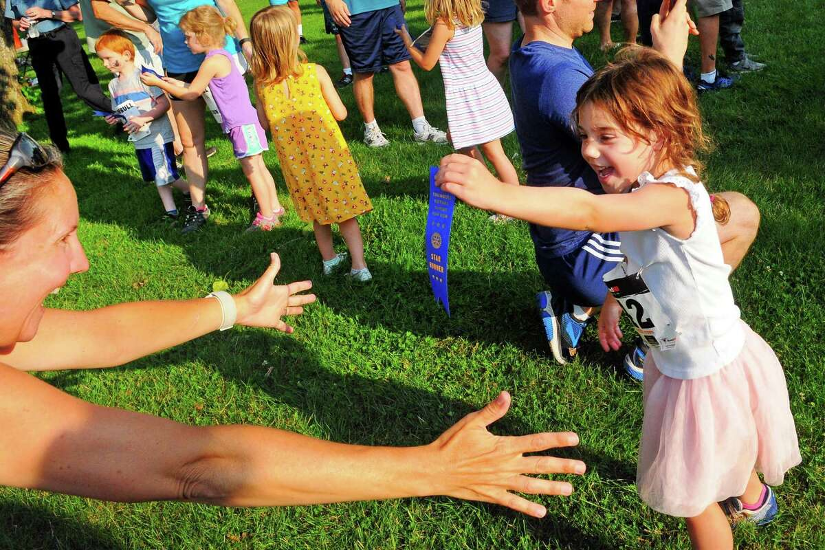 Mimi Voccola, 4, of Trumbull, runs to her mom Jenniffer to show her the ribbon she got in the Kids Fun Run during the Sunset Run at Twin Brooks Park in Trumbull, Conn., on Thursday July 27, 2019. The annual Rotary Club of Trumbull fundraiser includes a kids fun run, 5k run, and one mile health walk as well as games, facepainting, pizza, watermelon, music and more.