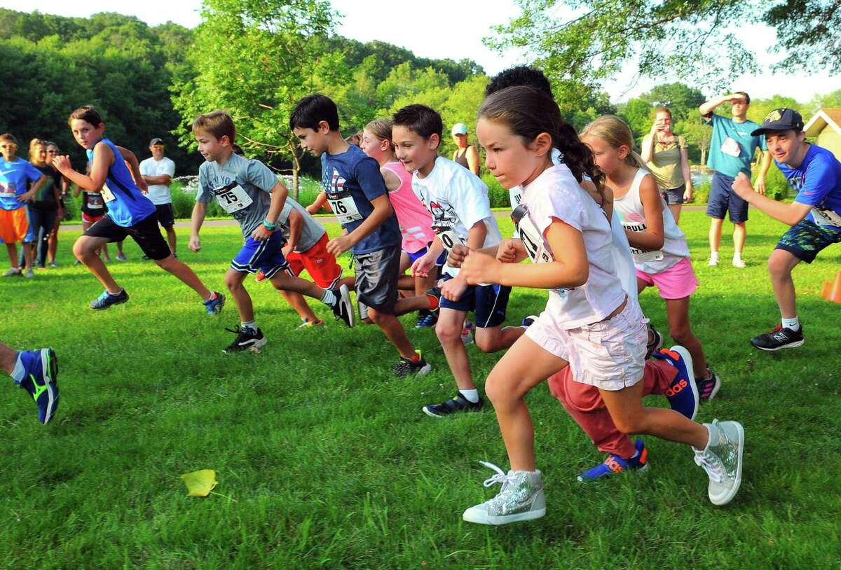 Siena Vitale, 6, of Trumbull, takes off from the starting line with other children in the Kids Fun Run during the Sunset Run at Twin Brooks Park in Trumbull, Conn., on Thursday July 27, 2019. The annual Rotary Club of Trumbull fundraiser includes the kids fun run, 5k run, and one mile health walk as well as games, facepainting, pizza, watermelon, music and more.