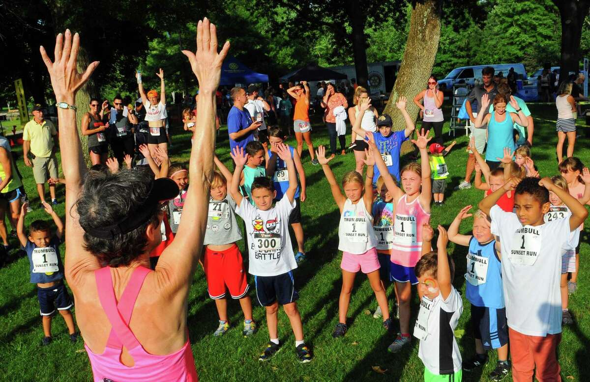 Donna Cramond leads kids in some warmup stretches before the start of the Kids Fun Run during the Sunset Run at Twin Brooks Park.
