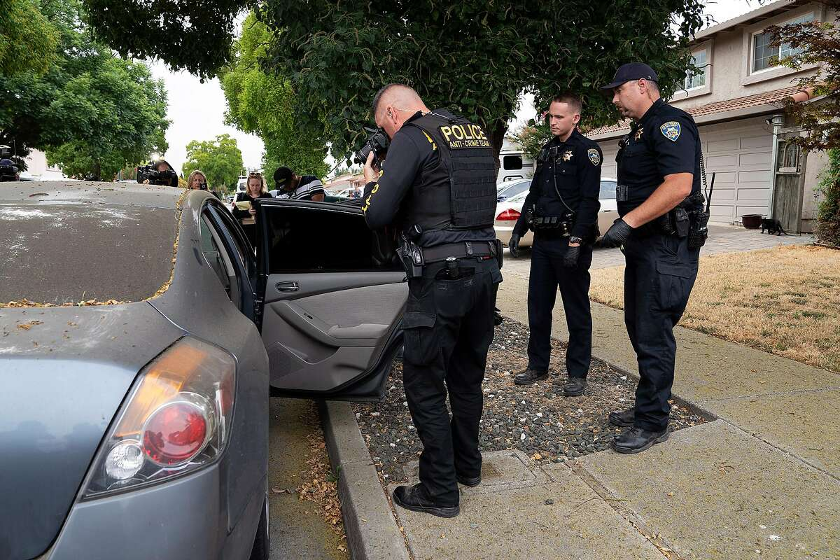 Gilroy Police Department officers search a gray Nissan Altima parked outside the family home of Gilroy Garlic Festival shooting suspect Santino William Legan.