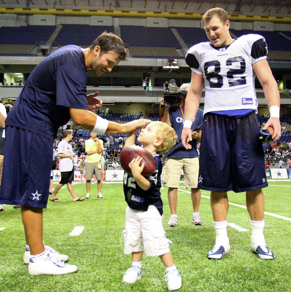 FOR SPORTS - Dallas Cowboys' quarterback Tony Romo (from left) high-fives CJ Witten as his dad Dallas Cowboys' tight end Jason Witten looks after afternoon practice Saturday Aug. 8, 2009 at the Alamodome. (PHOTO BY EDWARD A. ORNELAS/eaornelas@express-news.net)