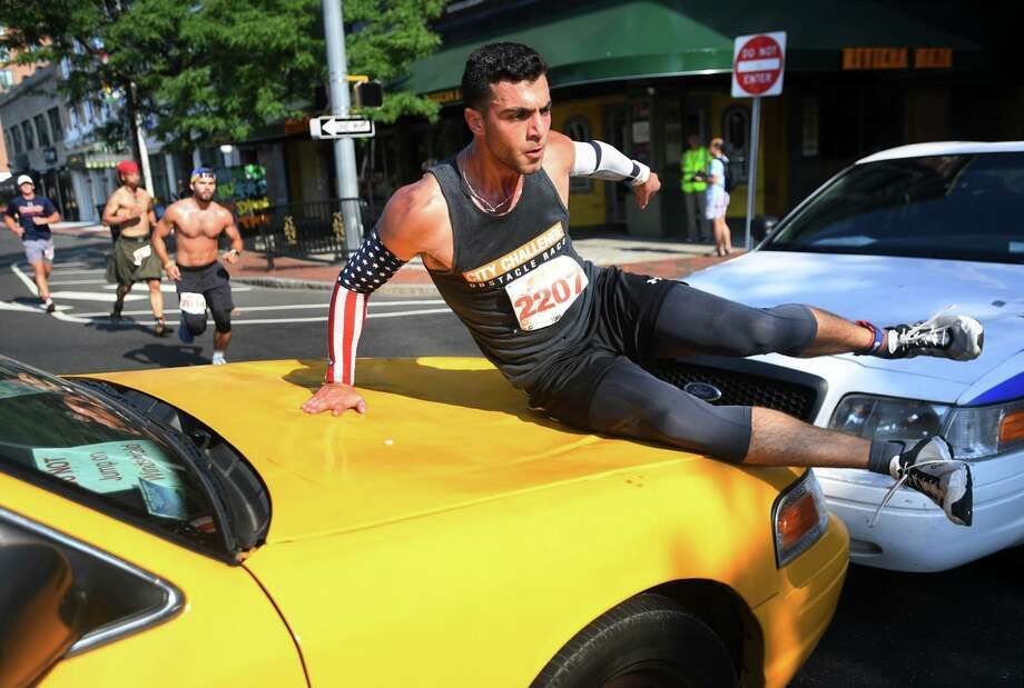 Donald Benjamin, of West Long Branch, N.J., slides across the hood of a taxi cab, one of twenty-three obstacles to overcome during the inaugural City Challenge Obstacle Race in downtown Stamford on Sunday. Photo: Brian A. Pounds / Hearst Connecticut Media / Connecticut Post