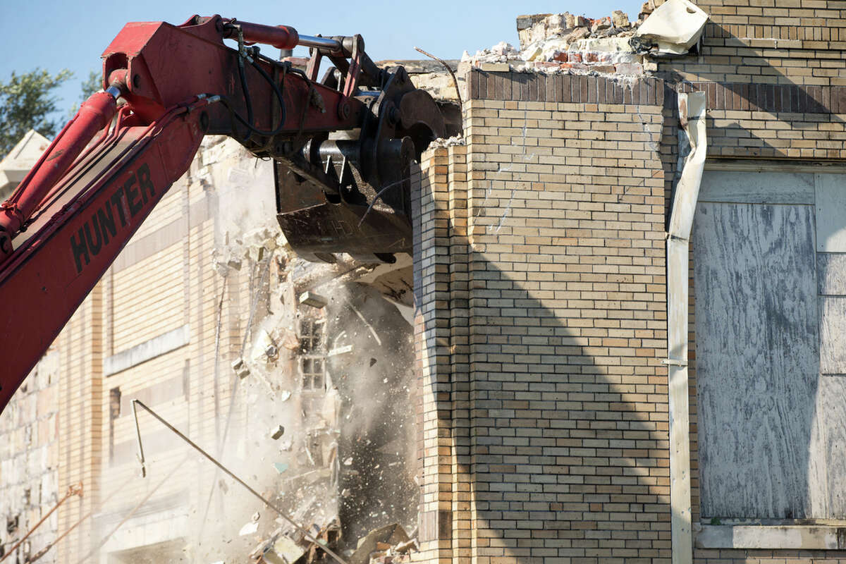An excavator tears down a side of old Beacon Hill Elementary, Wednesday, July 24, 2019 in San Antonio. Victoria Cavazos, a mother of a 1st grader and pre-k student