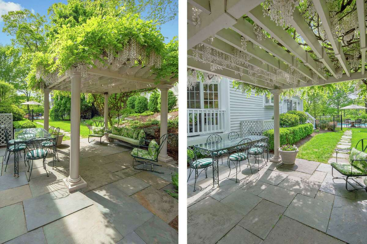 The beautifully landscaped backyard encourages indoor-outdoor living and entertaining, and includes a terrace under a pergola draped with wisteria vines surrounded by rock gardens.