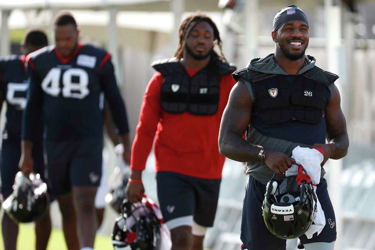 Houston Texans running back Lamar Miller, far right, walks onto the practice field during training camp at the Methodist Training Center on Monday, July 29, 2019, in Houston.