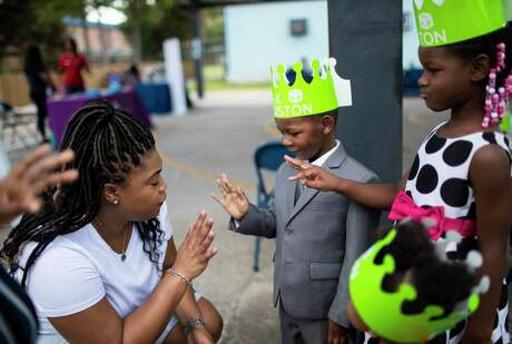Wesley Elementary School assistant principal LaKia Jackson, left, asks Micah Shivers, 3, and his sisters Nyla Shivers, 5, and Paris Shivers, 2, for their ages during a visit to the Wesley Elementary School to possibly enroll Micah on Saturday, July 27, 2019, in Houston.