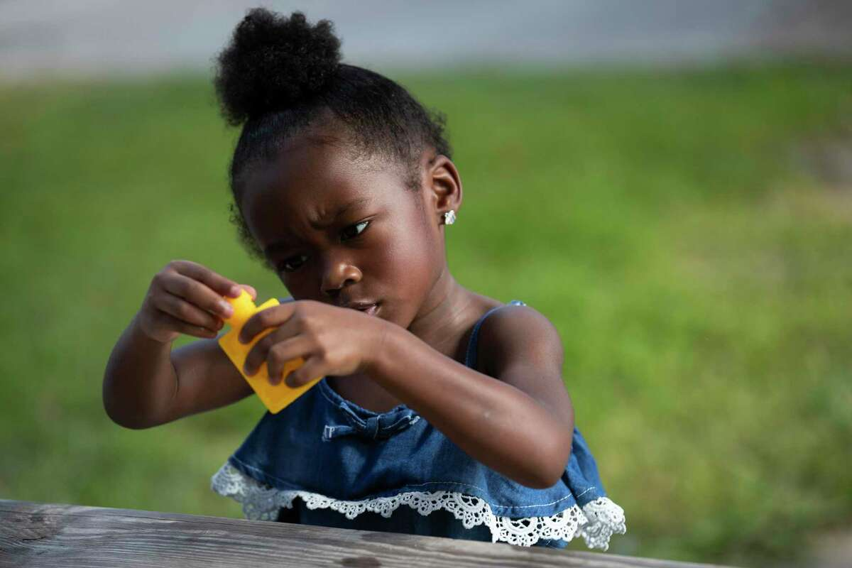 Bailee Houston, 3, observes a bottle of bubbles very seriously during a visit to the Wesley Elementary School with her mother on Saturday, July 27, 2019, in Houston.