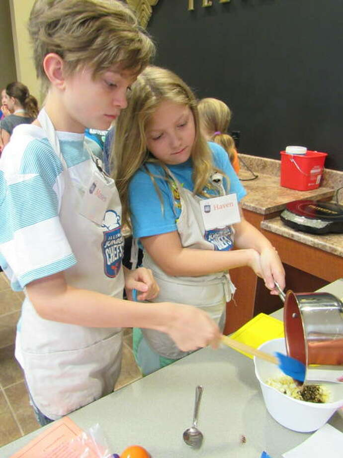 Jr. Chefs Moses and Haven Davenport add ingredients for the Tic-Tac-Taco Mix recipe at the Illinois Jr. Chef Camp in Jerseyville.