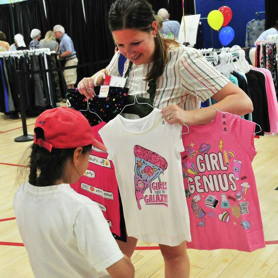 Lauren Atkins Yurch, a volunteer personal shopper, helps a shopper chose the perfect pink tee shirt. All of the clothes in the Back to School Shop are brand new, and purchased by volunteer shoppers throughout the year with funds raised from community donors. Photo: Elaine Osowski