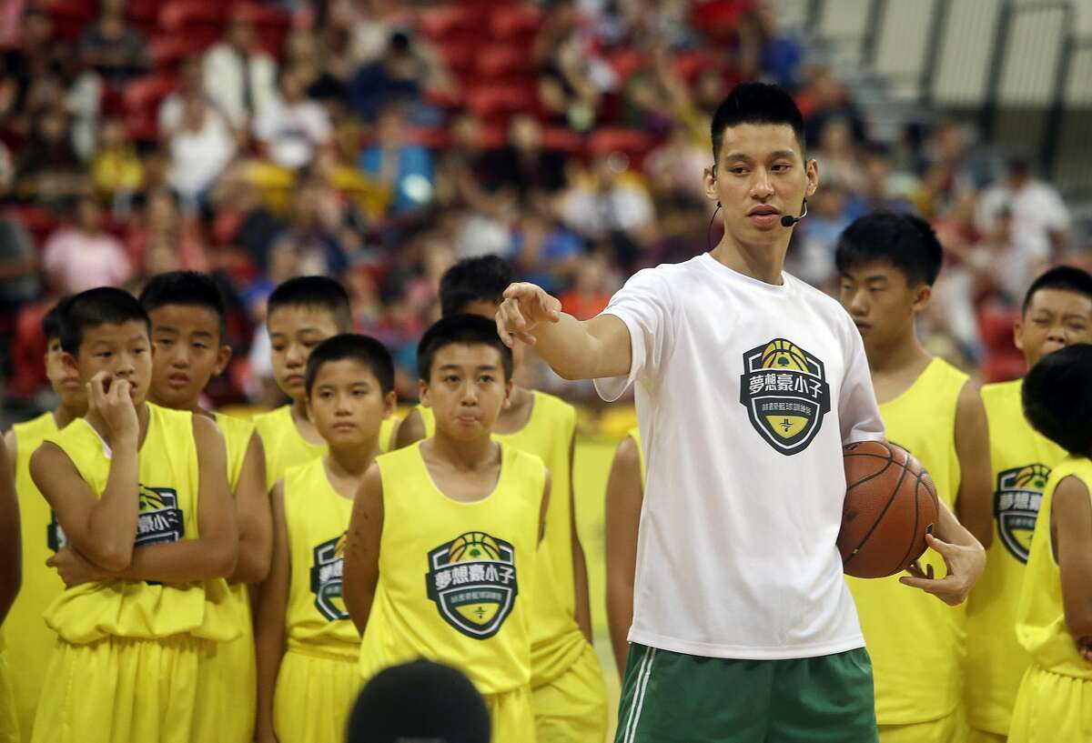 Jeremy Lin talks to young Taiwanese players during a basketball clinic in Taipei, Taiwan, in 2019.