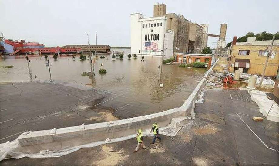 The portion of downtown Alton near the intersection of East Broadway and Piasa Street was a flooded mess Monday, June 3. The city flood wall kept a the majority of water from reaching downtown bussinesses. Illinois is now tallying damages from spring flooding to see if it totals $19 million to trigger federal assistance. Photo: John Badman | The Telegraph