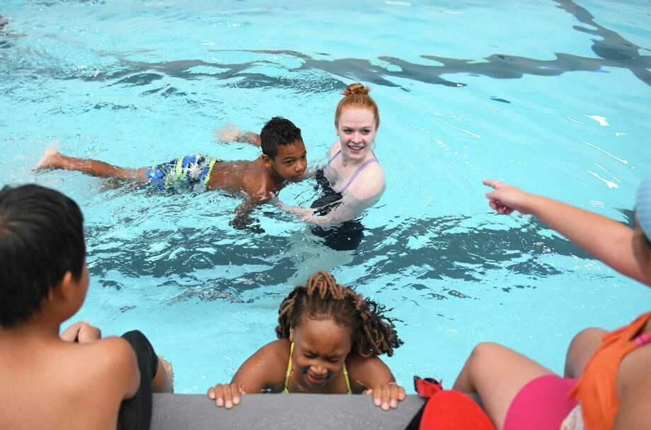 Stamford's Nolan Kinlock, 8, floats with swim instructor Kate Nusslein during the ZAC Foundation swim camp at the Boys & Girls Club of Stamford Yerwood Center in Stamford, Conn. Monday, July 29, 2019. More than 100 Stamford-area five- to nine-year-olds are participating in a four-day long water safety camp organized by The ZAC Foundation, which was established by Karen and Brian Cohn after the loss of their 6-year-old son Zachary Archer Cohn in a swimming accident in 2007. Nearly 15,000 other kids across the country have participated in ZAC camps that combine classroom instruction with swimming lessons and opportunities to learn important skills from first responders. Photo: Tyler Sizemore / Hearst Connecticut Media / Greenwich Time