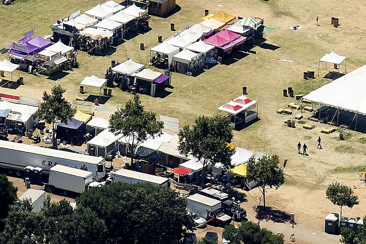 In this aerial photo, emergency personnel, right, walk among vendor booths at Christmas Hill Park, Monday, July 29, 2019, in Gilroy, Calif., the site of a shooting the day before at the Gilroy Garlic Festival. Authorities on Monday were searching for answers to why a 19-year-old opened fire on a popular food festival less than a mile from his parents' home in California, killing two children and another man, but believe many more people would have died if officers patrolling the event had not stopped the gunman so quickly. (AP Photo/Noah Berger)