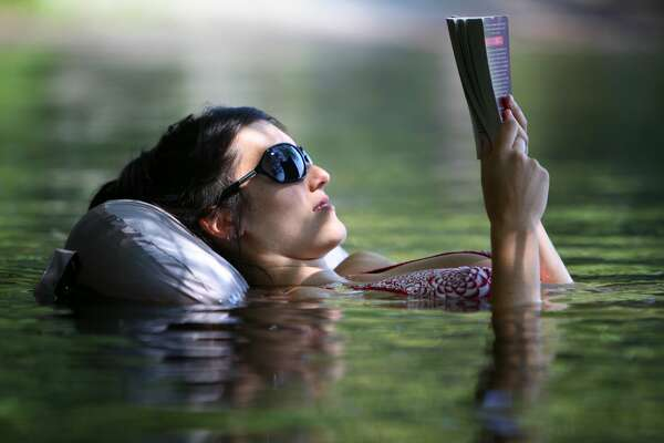 """Mia Robert of Seattle reads a book while floating on an inflatable seat she purchased before her trip to the park. """"I got the last one,"""" she said. Robert was trying to keep cool at Greenlake Park during a record heat wave in Seattle on Wednesday July 29, 2009. (Photo/Seattlepi.com, Joshua Trujillo)...."""