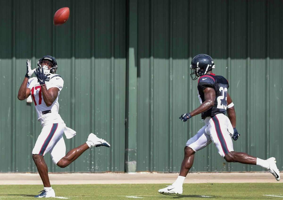 Houston Texans wide receiver Vyncint Smith (17) beats defensive back Johnson Bademosi (23) down field to make a catch during training camp at the Methodist Training Center on Saturday, July 27, 2019, in Houston.