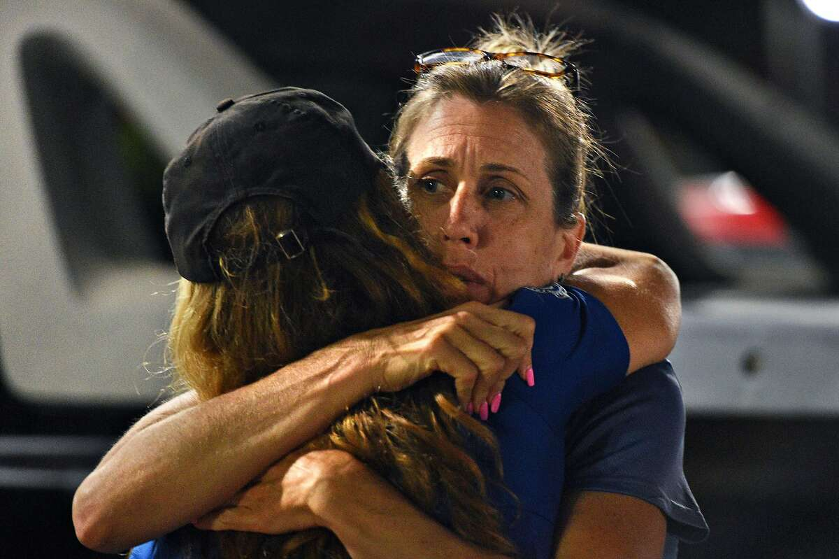 Unidentified women hug at Gavilan College - Gilroy Campus, the site of a reunification area, after a shooting during the Gilroy Garlic Festival on July 28, 2019.