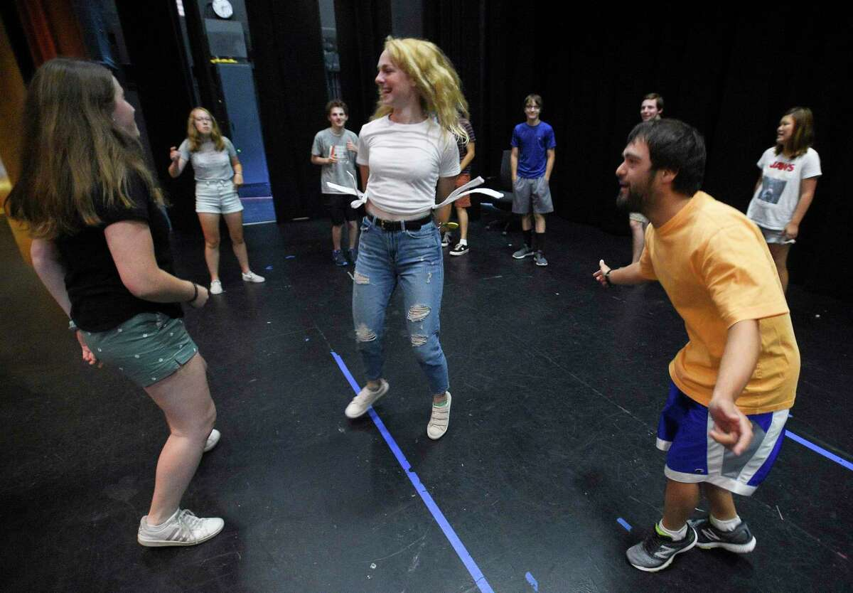Danny Clark dances with volunteers Hannah Doyle and Cameron Kittell as they and other cast members, warm up on stage during the Off Beat Players rehearsal for Joseph and the Amazing Technicolor Dreamcoat on July 19, 2019 at the Performing Arts Center of Greenwich Country Day School in Greenwich, Connecticut. Off-Beat Players, is a Greenwich-based nonprofit theater company, that provides young adults with disabilities the opportunity to participate in a performing arts program. The company performs fully staged musicals with a live orchestra each summer.