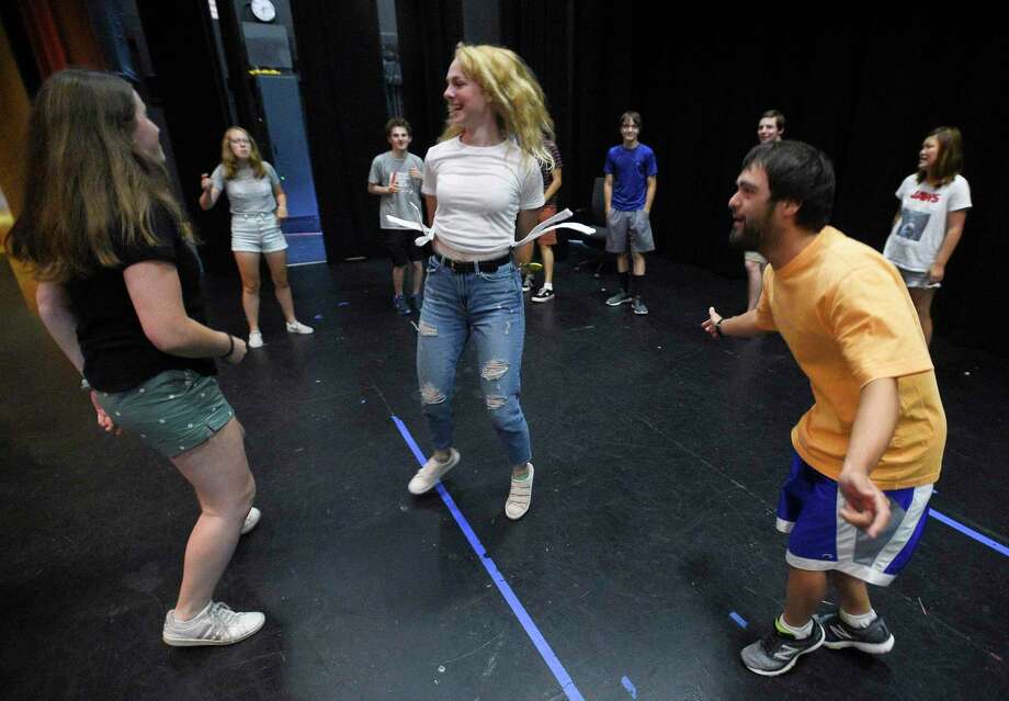 Danny Clark dances with volunteers Hannah Doyle and Cameron Kittell as they and other cast members, warm up on stage during the Off Beat Players rehearsal for Joseph and the Amazing Technicolor Dreamcoat on July 19, 2019 at the Performing Arts Center of Greenwich Country Day School in Greenwich, Connecticut. Off-Beat Players, is a Greenwich-based nonprofit theater company, that provides young adults with disabilities the opportunity to participate in a performing arts program. The company performs fully staged musicals with a live orchestra each summer. Photo: Matthew Brown / Hearst Connecticut Media / Stamford Advocate