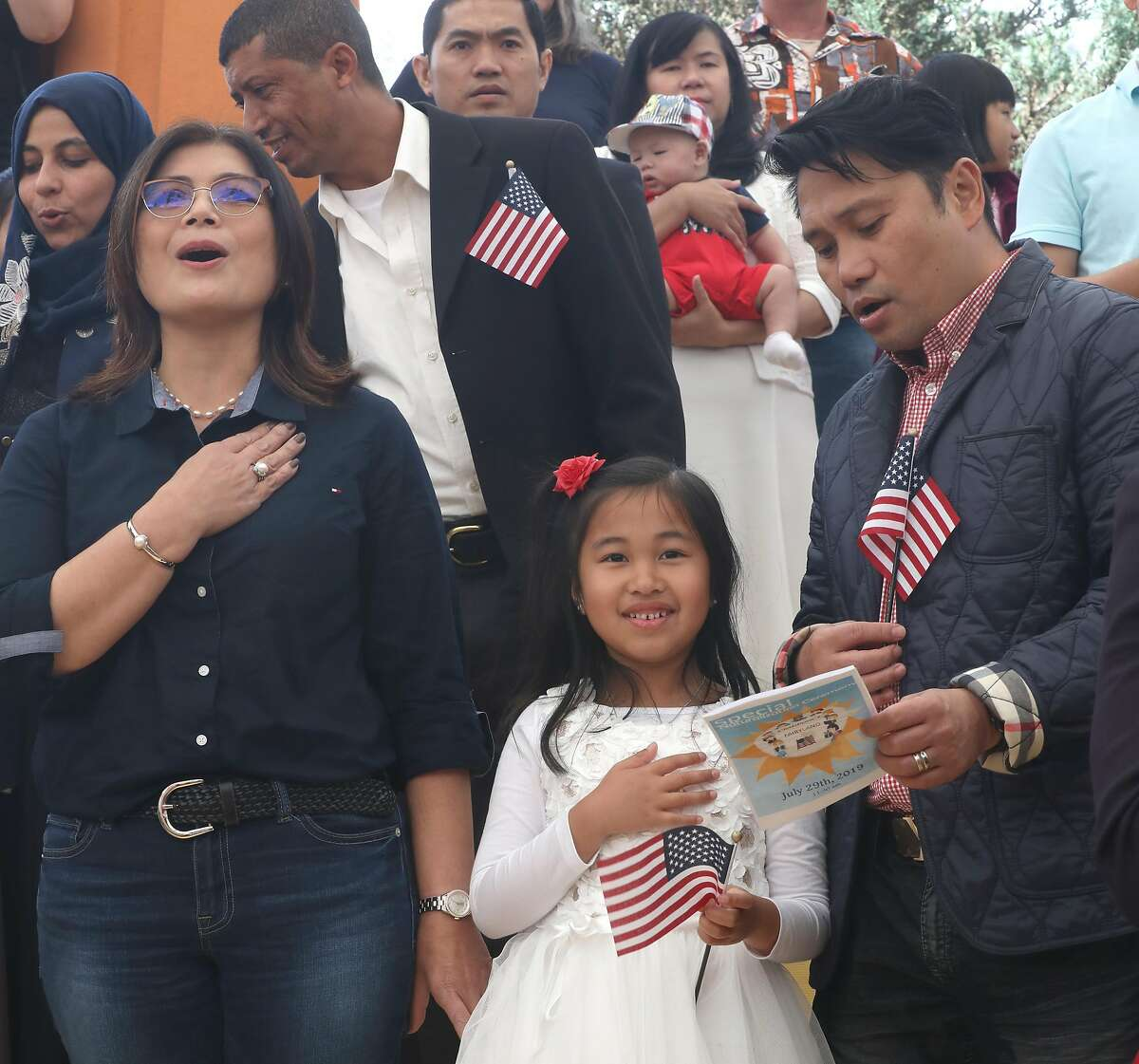 Isabella Basinang (middle), 6 years old, from Daly City says the pledge of allegiance next to her parents Marienilla Basinang (left) and Glen Basinang (right) at Children's Fairyland on Monday, July 29, 2019 in Oakland, Calif. He was one of twenty-six children ages 2-13 (from 13 countries) receiving certificates of citizenship at Children�s Fairyland from the U.S. Citizenship and Immigration Services.