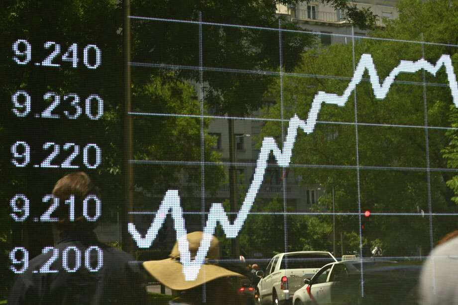 (FILES) In this file photo taken on June 07, 2019 people walk past a screen showing the IBEX 35 stock market index of Spain's principal stock exchange outside the Bank of Spain (Banco de Espana) in Madrid. - The world's main financial institutions have all upped their growth forecasts for Spain in 2019 over the past weeks, after the economy at the start of the year fared better than expected. (Photo by GABRIEL BOUYS / AFP)GABRIEL BOUYS/AFP/Getty Images Photo: GABRIEL BOUYS, Contributor / AFP/Getty Images / AFP or licensors