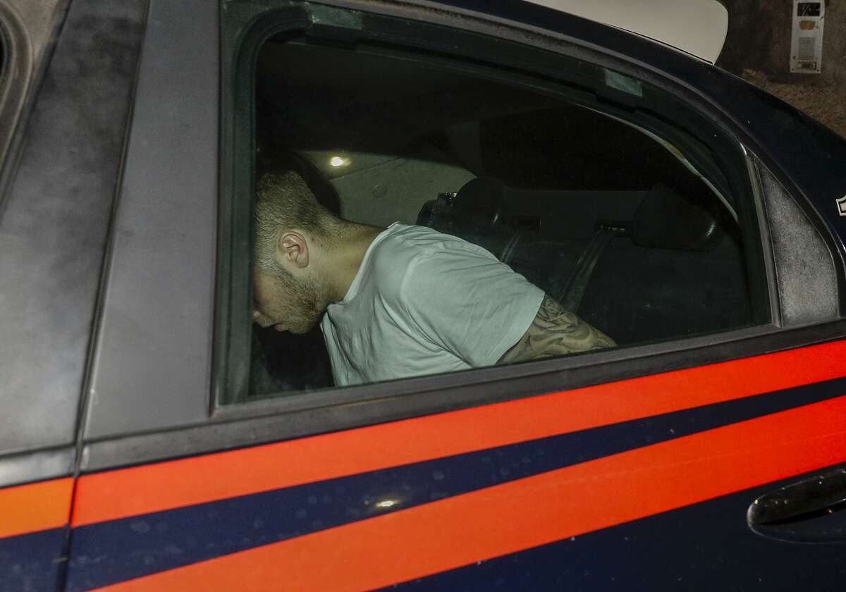 CORRECTS IDENTIFICATION OF THE MAN TO FINNEGAN LEE ELDER - American teenager Finnegan Lee Elder, who was allegedly questioned in the case of a slain Carabinieri policeman is seen on a Carabinieri car as it leaves a police station, in Rome, early Saturday morning, July 27, 2019. A young American tourist has confessed to fatally stabbing an Italian paramilitary policeman who was investigating the theft of a bag and cellphone before dawn Friday, the Italian news agency ANSA and state radio reported. (AP Photo/Andrew Medichini)