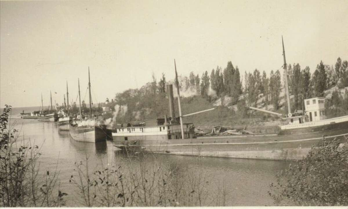 One of the main ways to transport goods made in Manistee in 1926 was with the use of schooners that are shown lining the Manistee River channel in this photograph.
