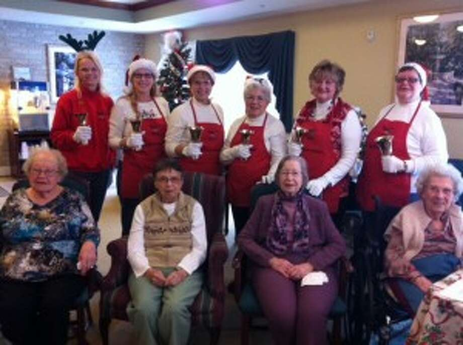 Green Acres residents Mildred Dierking, Mary Allen, Margaret Bryan and Virginia Caro sit in front of the Bells of Praise during a performance by Carol Worch, dee Kula, Sheryl Guenhardt, Karen Kimble, Marianne Blair and Donna Gamache on Dec. 16 at the assisted-living home. (Courtesy photo)