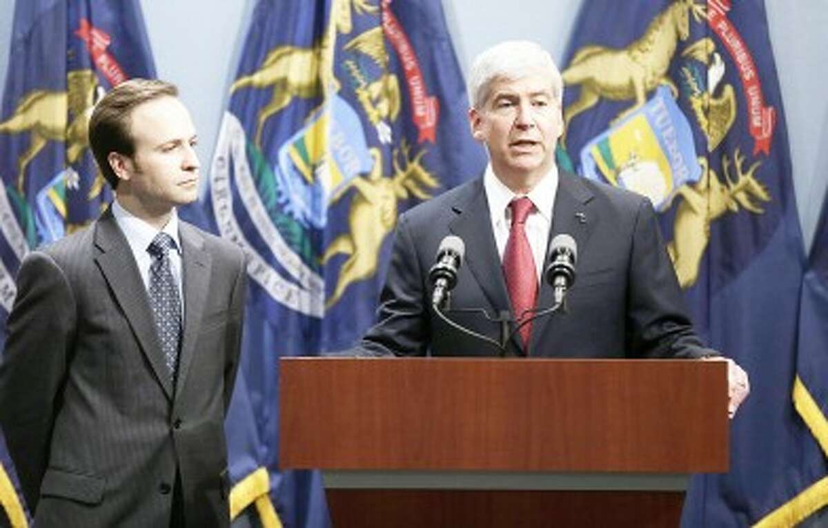 After signing the right-to-work law, Gov. Rick Snyder, right, speaks at a news conference in Lansing. (Courtesy Photo)
