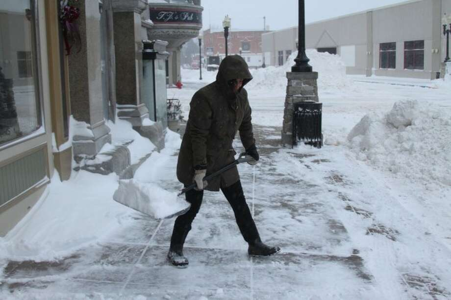 Jill Popielarz shovels off the sidewalk in front of Snyder's Shoes on Friday morning clearing a way for the customers. Manistee was hit with several inches of snow and lots of blowing snow Thursday evening and into Friday morning.