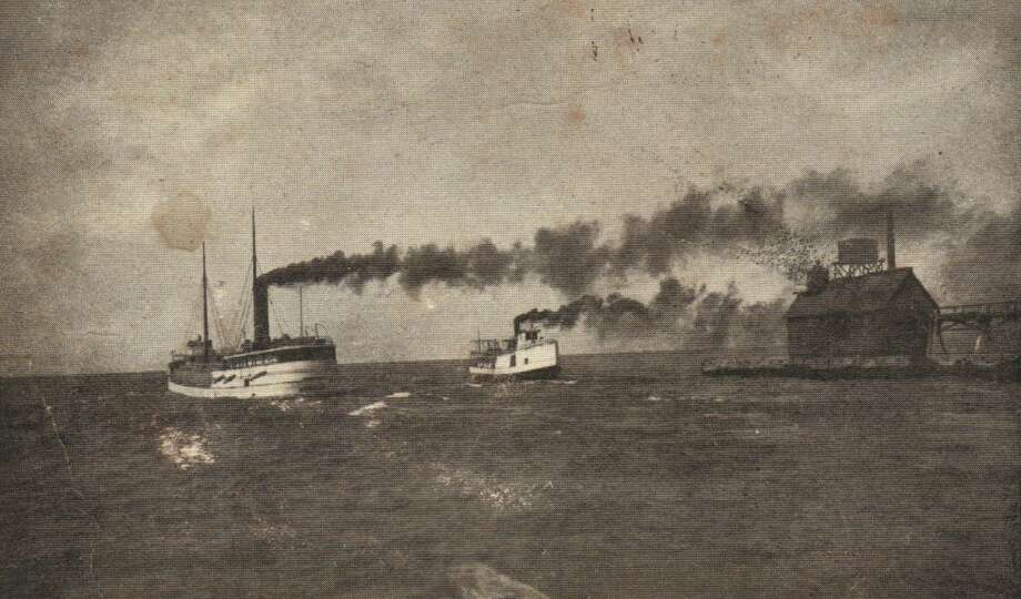 In the late 1800s a steamship and tugboat enter Manistee harbor. (Courtesy Photo/Manistee County Historical Museum)