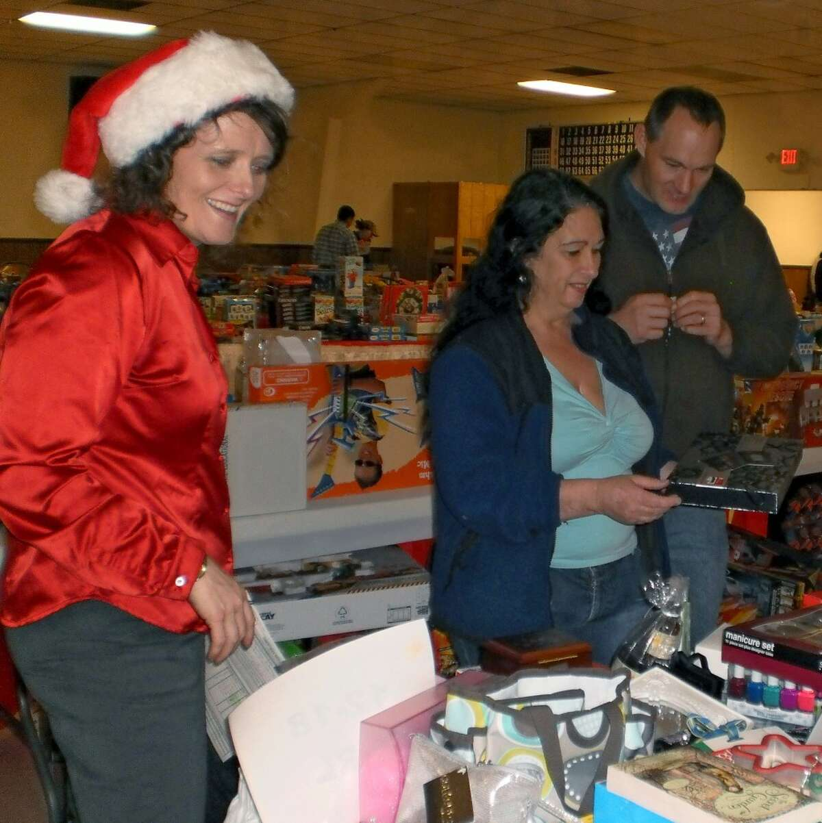 FiveCAP Community Support Services Worker Julie Ingison (left) helps Manistee County residents Carolyn and Paul Braun pick out Christmas presents for their four children during the Toys for Tots/Gifts for Teens distribution.(Courtesy photo)