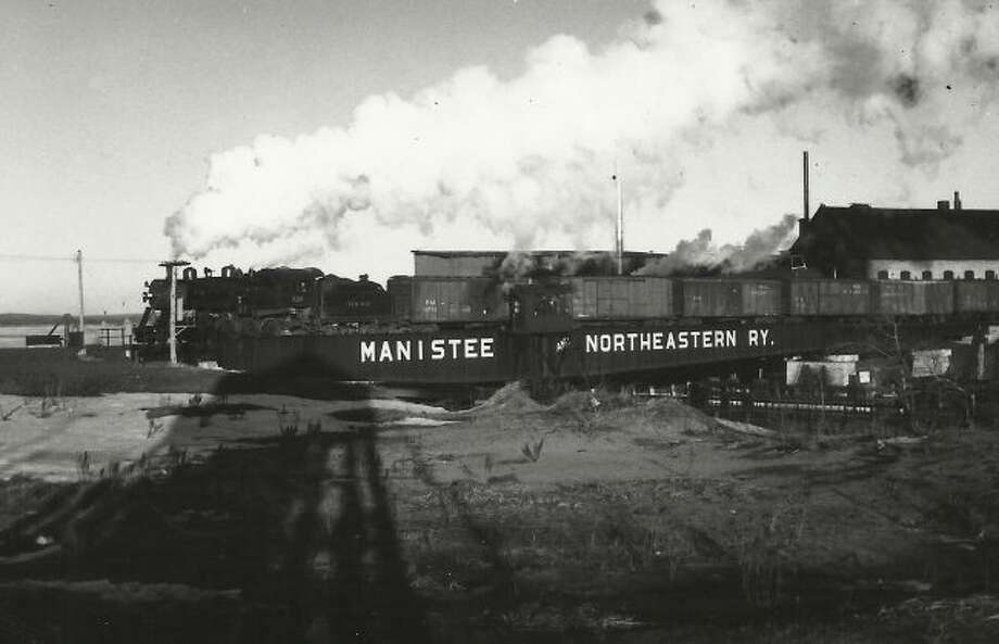 The railroad bridge of the Manistee and Northeastern Railroad over the Manistee River Channel is shown in this photograph from the early 1920s.