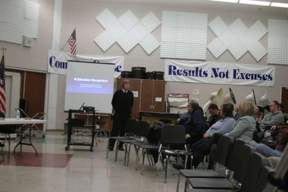 Apple representative Calvin Clark speaks to the Manistee Area Public Schools Board of Education on Manistee High School being an Apple Designated school.