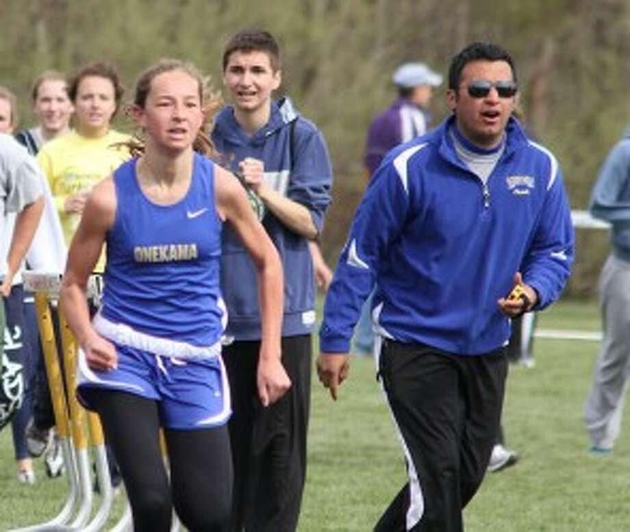 Onekama boys track and field coach Anthony Torres (right) cheers on Keena Gilbert during a meet last season. Torres resigned after two seasons with the co-op Portagers. (Dylan Savela/News Advocate file photo)