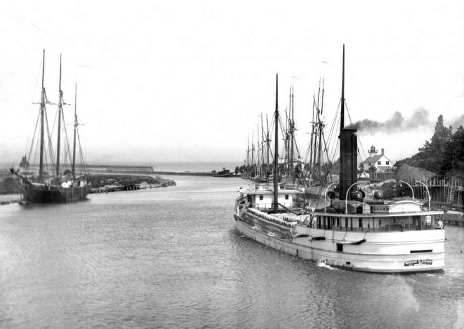 A steamer leaves the Manistee Harbor in the early 1900s showing a view of what the entrance looked like at that time.