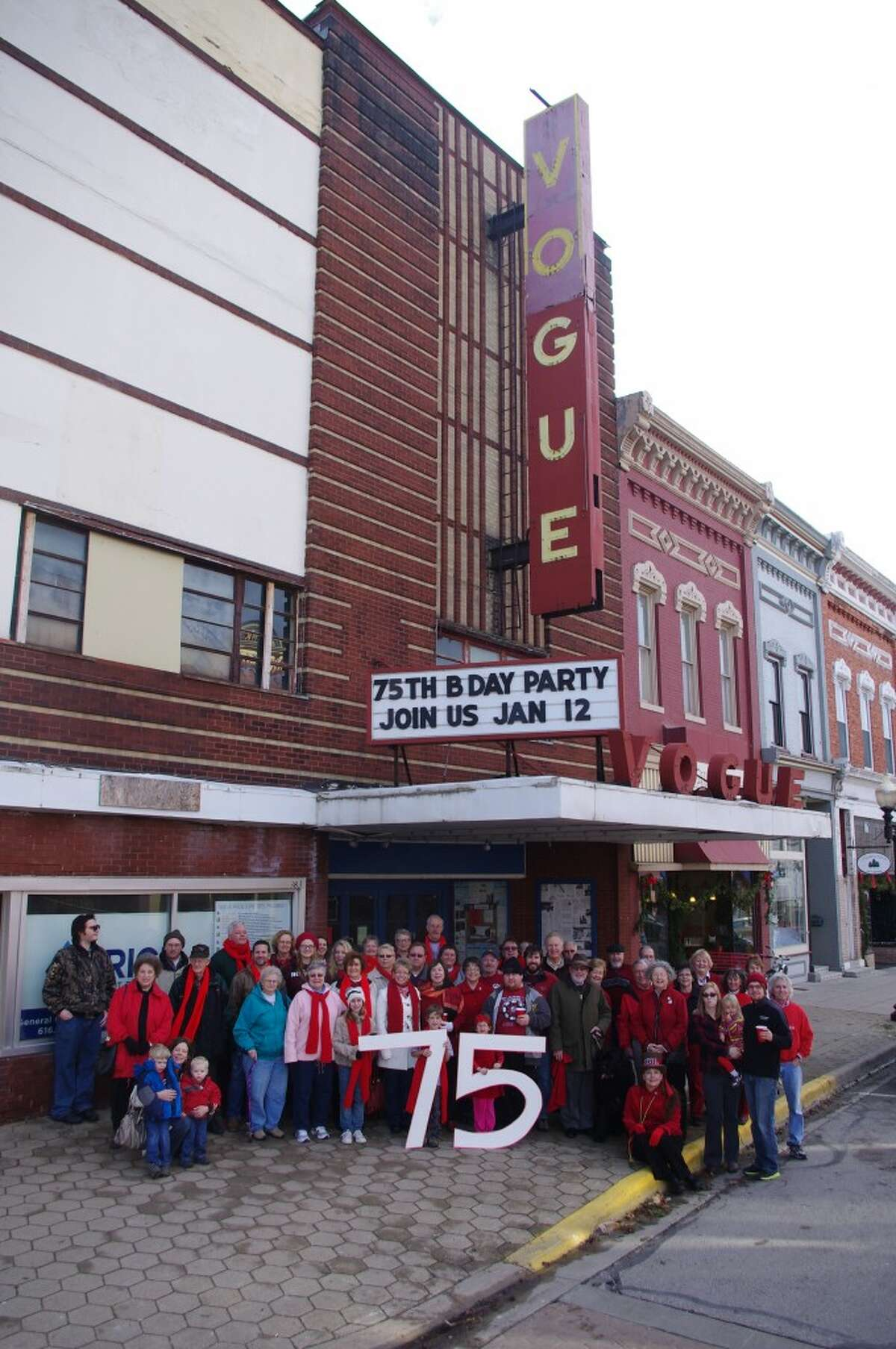 A crowd of people celebrating the Vogue Theatre's 75th birthday gather to have their photo taken Saturday in front of the theater. (Dave Yarnell/News Advocate)