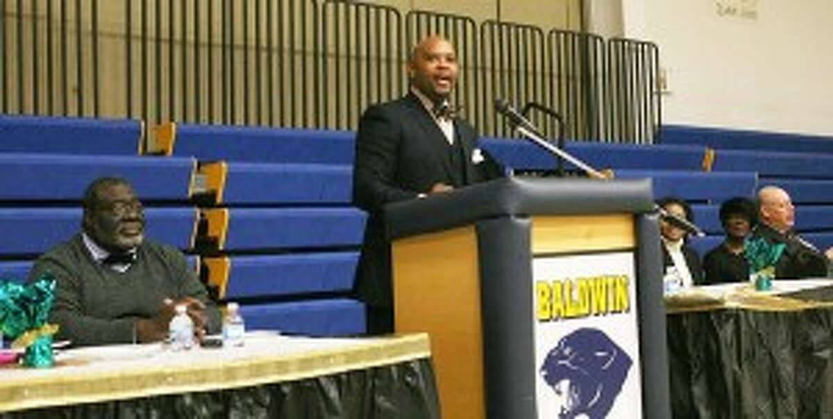 """Keynote speaker Andrei Nichols reads his speech """"The American Dream Yet Unfulfilled for Peace and Justice"""" at the Martin Luther King Jr. commemoration ceremony in Baldwin on Sunday."""