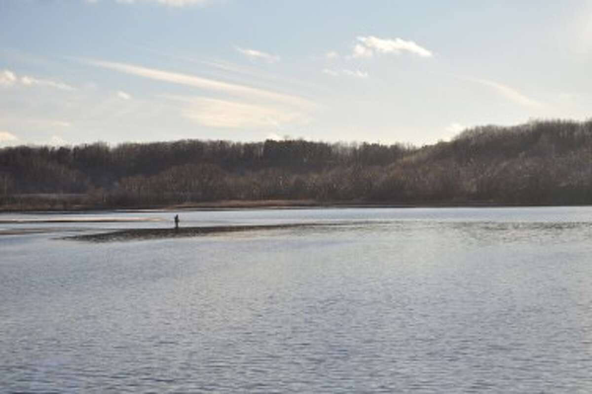 A man wades out into Manistee Lake to fish near Stronach.