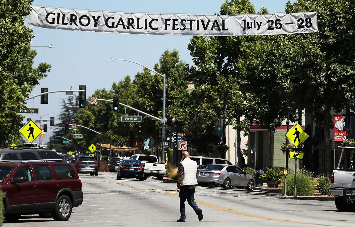 A man walks beneath a sign advertising the nearby Gilroy Garlic Festival on July 29, 2019 in Gilroy, California.