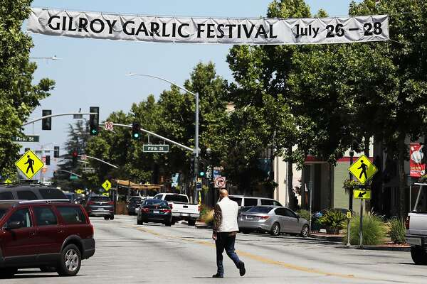 GILROY, CALIFORNIA - JULY 29: A man walks beneath a sign advertising the nearby Gilroy Garlic Festival after a mass shooting took place at the event yesterday on July 29, 2019 in Gilroy, California. Three victims were killed and at least a dozen were wounded before police officers killed the suspect. (Photo by Mario Tama/Getty Images)