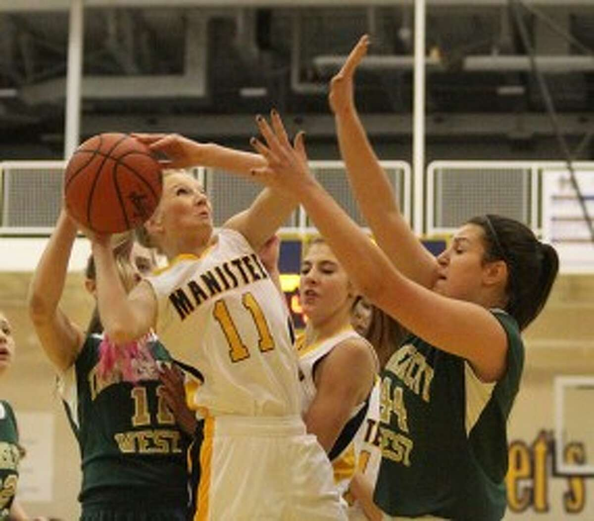 Manistee sophomore Annie Fuller (11) gets off a shot in between TC West's Katie Placek (11) and Paris Wagner (44) during the first half of Monday's game. (Matt Wenzel/News Advocate)